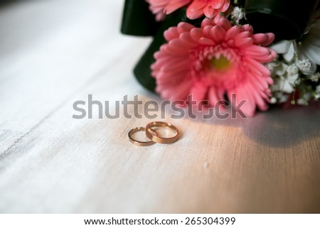 Bouquet and Two Wedding Rings. Goods for wedding. This photo is perfect for magazines, shops dealing with wedding dresses, ceremonies, bride, groom, marriage, jewelry. Can be used for wedding poster. - stock photo