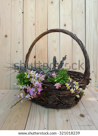 bouquet flowers in basket on wooden background.