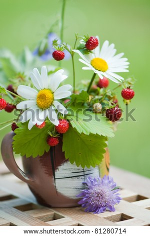 Bouquet from a camomile and wild strawberry - stock photo
