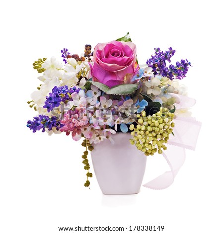 Bouquet from artificial flowers arrangement centerpiece in vase isolated on white background. Closeup. - stock photo
