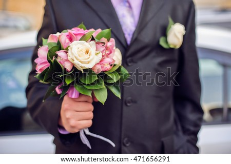 Bouquet in the hands of a man in a suit