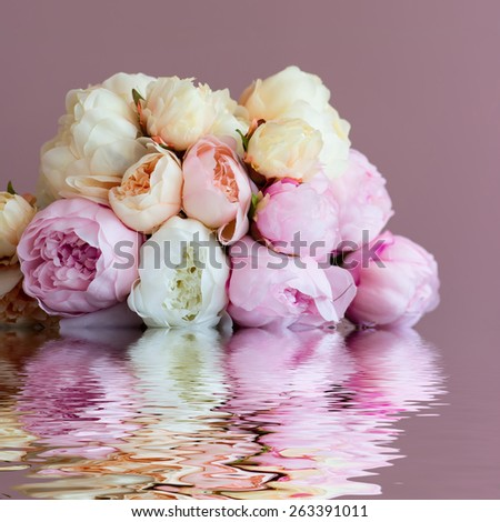 Bouquet made of artifical pink peony laying on a  watersurface. Shot against pink wall background. Shallow DOF. - stock photo