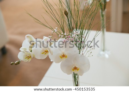 Bouquet made of white orchid stands on the white table - stock photo