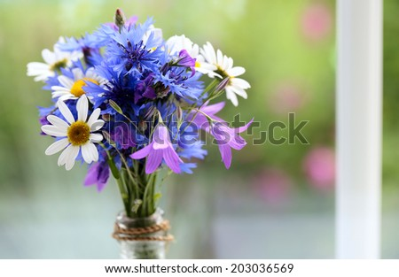 bouquet made of wildflowers on windowsill - stock photo