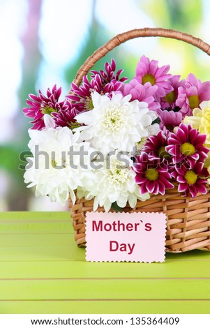Bouquet of beautiful chrysanthemums in wicker basket on table on bright background - stock photo