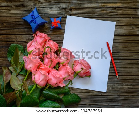 Bouquet of beautiful fresh pink roses with a blank love letter and pencil to write a Valentines message to a loved one with two blue gift boxes alongside - stock photo