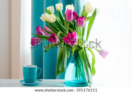 Bouquet of beautiful pink and yellow tulips in tiffany vase, cup with saucer. Free space for your text. - stock photo