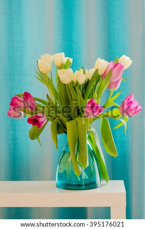 Bouquet of beautiful pink and yellow tulips in tiffany vase. Free space for your text. - stock photo