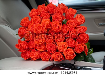 Bouquet of beautiful red roses in luxury car. Composition for a romance or anniversary. - stock photo