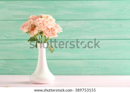 Bouquet of beautiful roses on a pink wooden table - stock photo