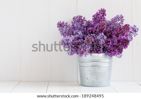 Bouquet of beautiful spring flowers of lilac in a vase on a white vintage wooden board, home decor in a rustic style - stock photo