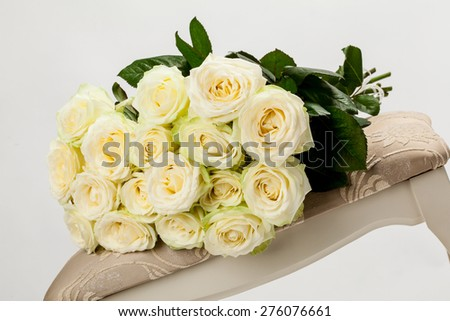 Bouquet of beautiful tea-roses on a banquette, neutral background - stock photo