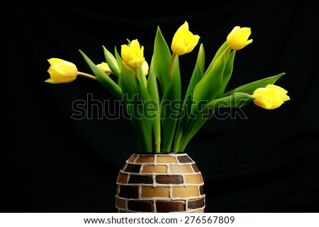 Bouquet of beautiful tulips yellow in ceramic vase isolated on black background - stock photo