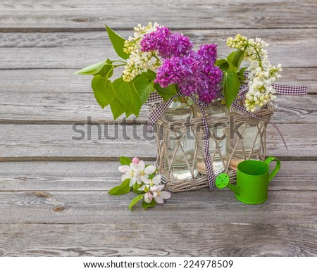 Bouquet of blooming lilacs and apple trees near decorative watering can on a wooden table