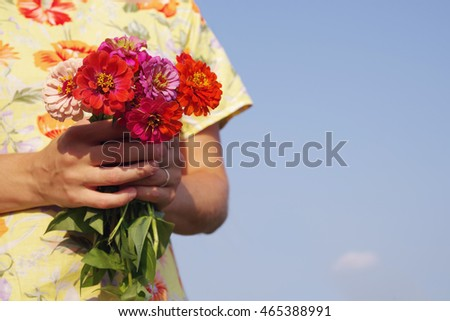 Bouquet of bright summer flowers in the girl's hands in a yellow dress against the blue sky. Festive bouquet