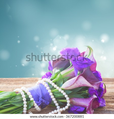 Bouquet of calla lilly and eustoma flowers  on wooden table border on blue  - stock photo