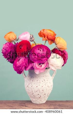 Bouquet of colorful ranunculus in an antic ceramic vase - stock photo