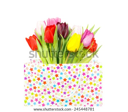 Bouquet of colorful tulips in a gift bag isolated on white - stock photo