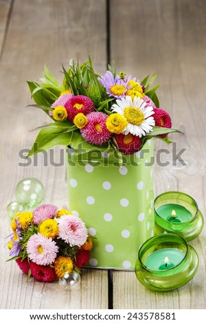 Bouquet of colorful wild flowers in green dotted can