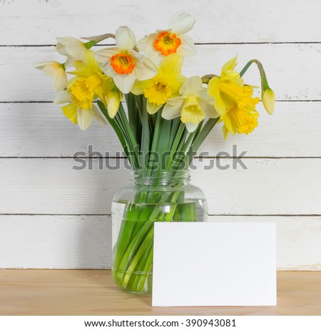 Bouquet of daffodilsin a glass jar with a blank greeting card on a wooden table in the background of the white wooden wall with copy space. Provence style. Square photo - stock photo