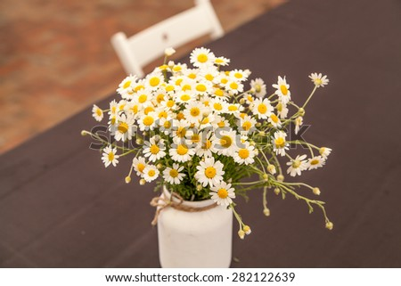 Bouquet of daisies in a white vase on a dark background