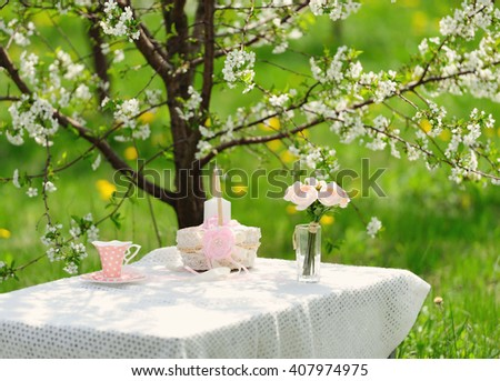 bouquet of delicate pink roses and  cup on the table in the blooming garden - stock photo