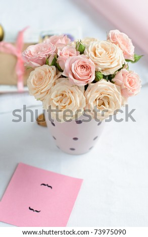 bouquet of delicate pink roses in a cup on the table - stock photo