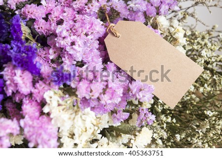Bouquet of dried flowers with blank paper tag on the wooden table - stock photo