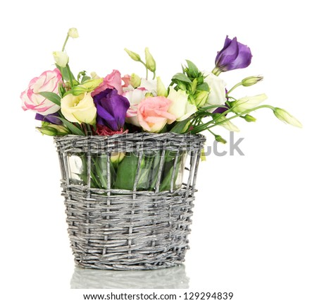 Bouquet of eustoma flowers in wicker basket isolated on white - stock photo