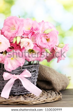 bouquet of eustoma flowers in  wicker vase, on wooden table, on green background - stock photo