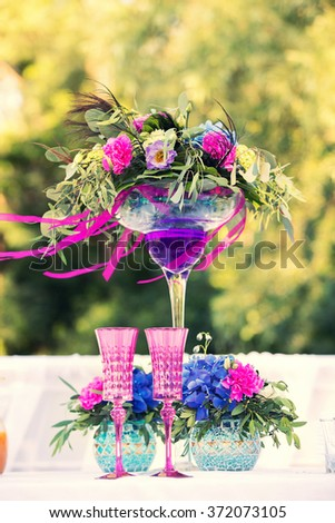 bouquet of flowers and couple of wedding glasses of pink color - stock photo