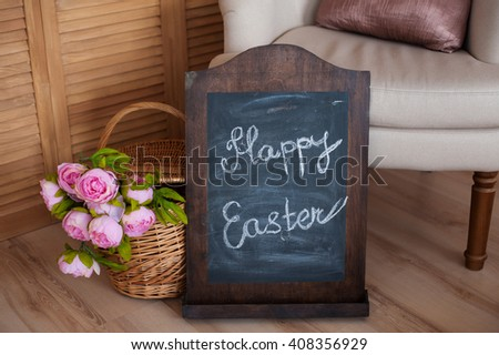 bouquet of flowers in a basket and words happy easter  on blackboard - stock photo