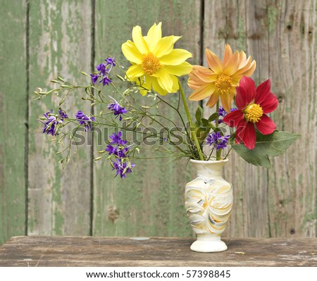 Bouquet of flowers in a ceramic vase on a background of an old wooden walls - stock photo