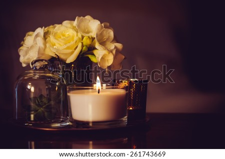 Bouquet of flowers in a vase, candles on a tray, vintage home decor on an a table, dark tones - stock photo