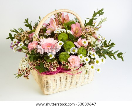 Bouquet of flowers in basket on white background - stock photo