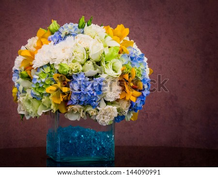 Bouquet of flowers in glass vase on grunge brown background - stock photo