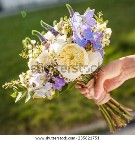 Bouquet of flowers in hand on a grass background. - stock photo