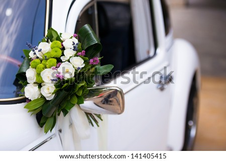 Bouquet of flowers on bridal car's mirror