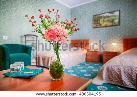 Bouquet of flowers on the table in hotel room. Selective focus on flower bouquet, hotel apartments. Double suit, two beds. Nobody in. Interior of hotel room.  - stock photo