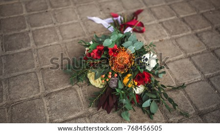 Bouquet of flowers red, yellow, green colors, on the ground