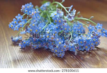bouquet of forget me nots lying on the wooden table