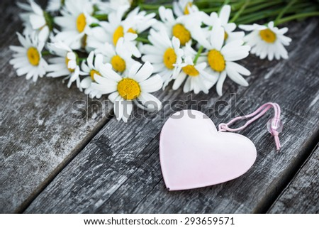 Bouquet of fresh camomiles with wooden hearts on old wooden table. Valentine's holiday romantic card concept. - stock photo