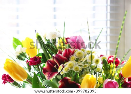Bouquet of fresh flowers by the window