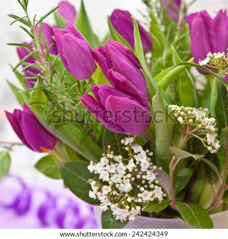 Bouquet of Fresh purple tulips and blooming branches - stock photo