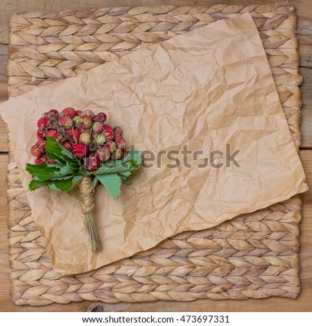 bouquet of fresh red strawberries on crumpled brown paper. text box.