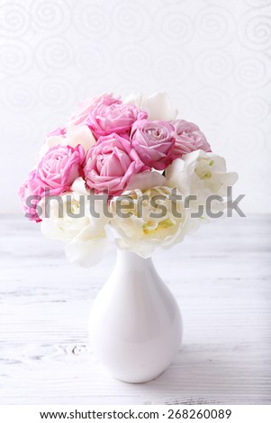 Bouquet of fresh roses and tulips on wallpaper background - stock photo