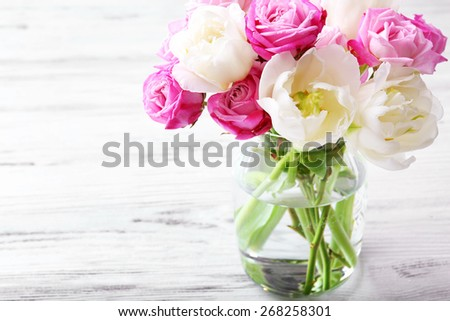 Bouquet of fresh roses and tulips on wooden background - stock photo