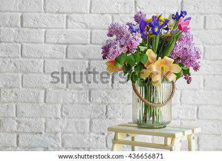 Bouquet of fresh spring flowers on brick wall background - stock photo