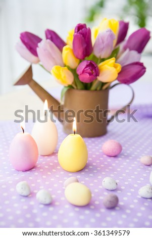 Bouquet of fresh tulips and easter treats on purple background - stock photo