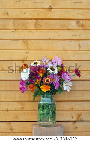 Bouquet of garden flowers in a glass jar on the background of the wooden wall of the old village house - stock photo